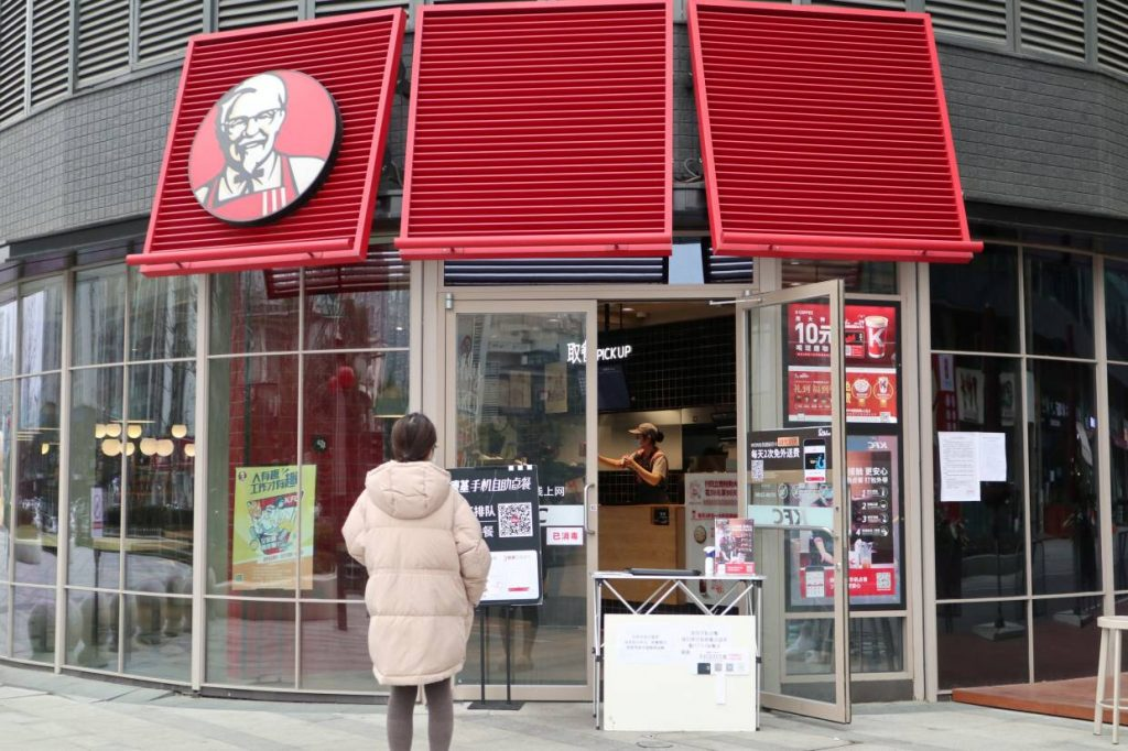 Một khách hàng đang đứng chờ bên ngoài để nhận đơn đặt hàng tại lối vào của nhà hàng KFC ở Thành Đô, tỉnh Tứ Xuyên, Trung Quốc (nguồn: https://www.reuters.com/)